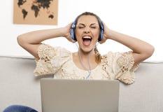 Ascolta la musica sul suo computer portatile Fotografia Stock Libera da Diritti