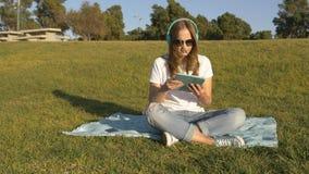 Ascoltando la musica dalla compressa nel parco sulla stuoia fotografia stock libera da diritti