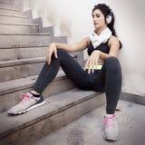 Ascoltare di rilassamento del giovane corridore femminile la musica Fotografia Stock