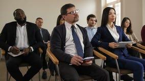 Ascoltatori di seminario di affari di Multiraced che fanno le note stock footage