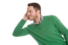 Ascolto isolato uomo curioso lateralmente su bianco. Fotografia Stock
