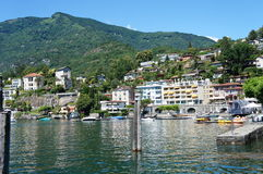 Ascona at Lake Maggiore. Part of Ascona at Lake Maggiore in Ticino, Switzerland; houses and forested mountains and in foreground the lake; blue sky Stock Image
