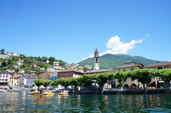 Ascona at Lake Maggiore, Switzerland. View from Lake Maggiore on Ascona in the canton of Ticino in Switzerland; houses and a church tower;  green plan trees on Royalty Free Stock Photography