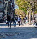 Ascona Schweiz - April 15, 2019: Folk som går med cyklistlädermode och cyklisthjälmar till och med den soliga staden arkivbilder