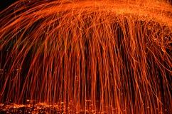 Ascuas ardientes que caen en oscuridad imagen de archivo