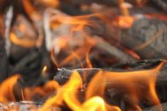 Ascuas de madera ardientes con las llamas Fotografía de archivo libre de regalías