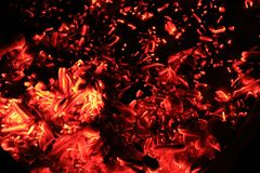 Ascuas rojas y anaranjadas brillantes de la hoguera en la noche fotos de archivo libres de regalías