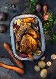 Ase el pavo o el pollo entero en cacerola vieja con las verduras imagen de archivo libre de regalías