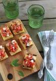 Ase a la parilla el polenta del maíz con el tomate, el queso Feta y la aceituna Fotos de archivo