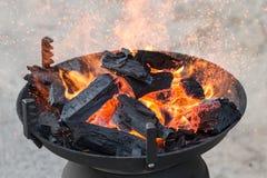 Ase a la parilla la parrilla, el carbón de leña y las llamas del fuego Foto de archivo libre de regalías