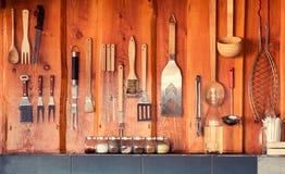 Ase a la parrilla, área del Bbq con las herramientas que cuelgan en la pared Imagen de archivo libre de regalías