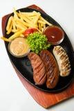 Ase a la parrilla las salchichas en la placa de madera con las patatas fritas y las salsas Fondo blanco Imagen de archivo
