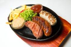 Ase a la parrilla las salchichas en la placa de madera con las patatas fritas y las salsas Fondo blanco Imagen de archivo libre de regalías