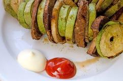 Ase a la parrilla las verduras en la placa blanca con el sause, la calabaza, la cebolla y MU imagen de archivo
