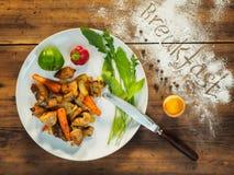 Ase las patatas con la carne y la lechuga en una placa blanca, visión superior Todavía vida de verduras en el fondo de la madera  Imagen de archivo