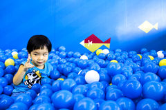 Asean boy counting ball in the playroom full of balls Royalty Free Stock Photos