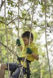 Asean boy nodes the rope and smiling happily in camp adventure Background blurry tree stock image