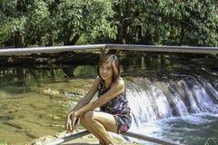 Asean-Frau und -wasser im Strom ist grün und hellgrüner Baum an den Kapo-Wasserfall-Vorderteilen parken, Chumphon in Thailand stockbild