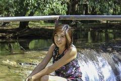 ASEAN-kvinnan och vatten i strömmen är gröna och ljusa - det gröna trädet på Kapo vattenfallför parkerar, Chumphon i Thailand royaltyfria bilder