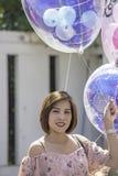 ASEAN-kvinnor rymmer en ballong i hand royaltyfri bild