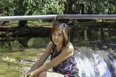 Asean woman and water in the stream is green and bright green tree at Kapo Waterfall Fores Park , Chumphon in Thailand.  royalty free stock images