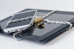 Asegurar smartphone y cadena y polea de la tableta Foto de archivo libre de regalías
