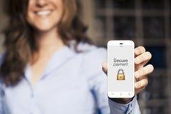 Asegure el mensaje del pago Mujer que muestra su teléfono móvil Foto de archivo