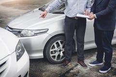 Asekuracyjnego agenta writing na schowku podczas gdy egzamininujący samochód po a Zdjęcie Royalty Free