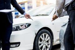 Asekuracyjnego agenta writing na schowku podczas gdy egzamininujący samochód po a Zdjęcia Royalty Free