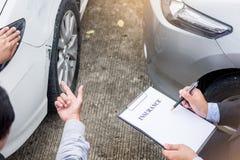 Asekuracyjnego agenta writing na schowku podczas gdy egzamininujący samochód po a Obraz Royalty Free