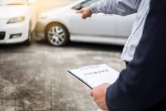 Asekuracyjnego agenta writing na schowku podczas gdy egzamininujący samochód po a Zdjęcie Stock