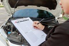 Asekuracyjnego agenta writing na ubezpieczenia samochodu egzamininować i dokumencie Obrazy Stock