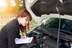 Asekuracyjnego agenta writing na ubezpieczenia samochodu egzamininować i dokumencie Fotografia Stock