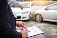 Asekuracyjny agent egzamininuje Uszkadzającego samochód i segregowania żądania Raportową formę Obraz Royalty Free