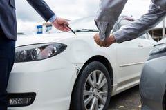 Asekuracyjny agent egzamininuje Uszkadzającego samochód i segregowania żądania Raportową formę Zdjęcie Royalty Free