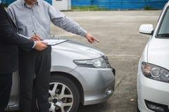 Asekuracyjny agent egzamininuje Uszkadzającego samochód i segregowania żądania Raportową formę Fotografia Royalty Free