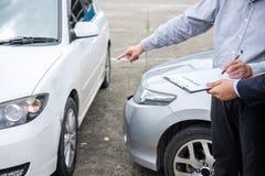 Asekuracyjny agent egzamininuje Uszkadzającego samochód i segregowania żądania Raportową formę Zdjęcie Stock