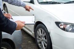 Asekuracyjny agent egzamininuje Uszkadzającego samochód i segregowania żądania Raportową formę Obrazy Stock
