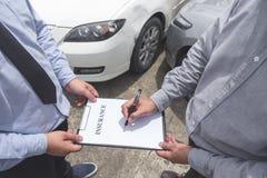 Asekuracyjny agent egzamininuje Uszkadzającego samochodu i klienta segregowania signatur Zdjęcie Stock