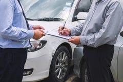 Asekuracyjny agent egzamininuje Uszkadzającego samochodu i klienta segregowania signatur Obrazy Stock