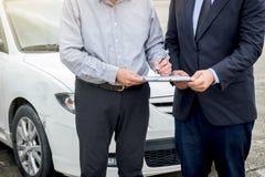 Asekuracyjny agent egzamininuje Uszkadzającego samochodu i klienta segregowania signatur Zdjęcia Stock