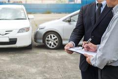 Asekuracyjny agent egzamininuje Uszkadzającego samochodu i klienta segregowania signatur Obraz Stock