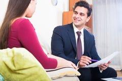 Asekuracyjny agent i klient dyskutuje zgoda terminy w livin Zdjęcia Stock
