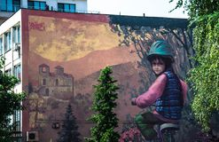 Asenovgrad, Plovdiv / Bulgaria – 08/01/2018: Street mural in Asenovgrad showing boy on a bicycle and Asen's Fortress stock photo