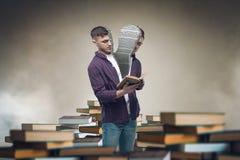 Aserrado en la media lectura del hombre entre los libros y los libros de texto Fotos de archivo
