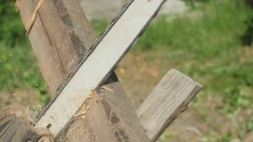 Aserrando a un tablero de madera con la motosierra, la vista lateral, proceso que asierra, el serrín de madera diferencia en dive almacen de metraje de vídeo