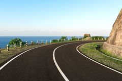 Asfalt kustweg die om de kromming van de klippenrand gaan Stock Foto's
