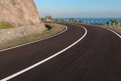 Asfalt kustweg die om de kromming van de klippenrand gaan Royalty-vrije Stock Foto's
