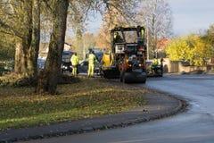Asfaltarbetarcraftsemen som lägger ny asfalt med tunga maskiner Royaltyfri Fotografi