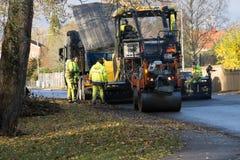 Asfaltarbetarcraftsemen som lägger ny asfalt med tunga maskiner Royaltyfria Bilder